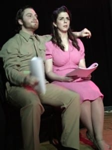 A man and woman sit together. He in GI clothing of the 1940's and she in Period dress. They hold scripts in hand