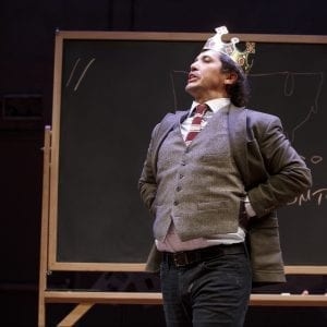 John Leguizamo in front of blackboard wearing a crown