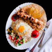 Persian Joojeh Kebab on a bed of Chelo and Fried Egg with Shirazi Salad