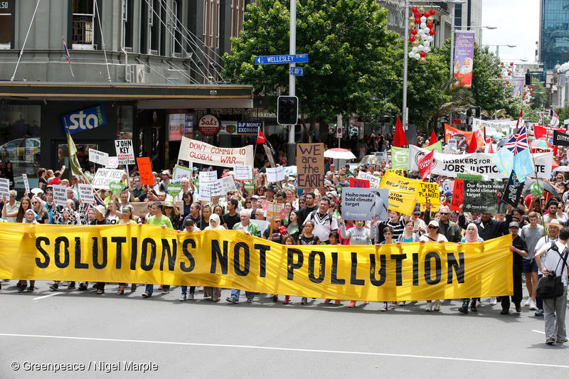 Participants in the 2015 Global Climate March hold a banner reading 'Solutions Not Pollution.' © Greenpeace / Nigel Marple
