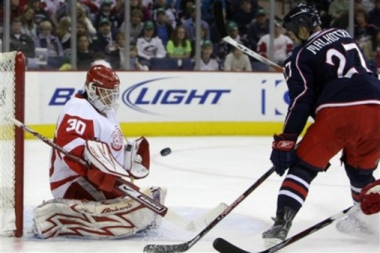 Detroit Red Wings' Chris Osgood, left, makes a save against Columbus Blue Jackets' Manny Malhotra during the second period of an NHL hockey game Sunday, March 15, 2009, in Columbus, Ohio. Photo courtesy of AP