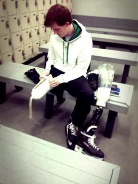 Ty putting on his prosthetic skate in the locker room.