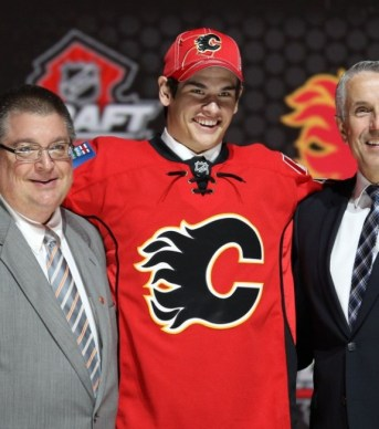 Sean Monahan tries to get his arm around Jay Feaster (Ed Mulholland-USA TODAY Sports)