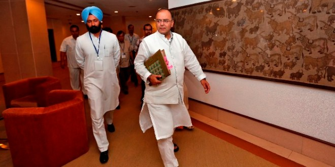 India's Finance and Defence Minister Arun Jaitley (C) arrives to attend a meeting with the finance ministers of Indian states on the Goods and Services Tax (GST) issues in New Delhi July 3, 2014. India's new government will seek to raise up to a record $11.7 billion in asset sales in its maiden budget this week, a senior government source said, bolstering state finances and buying time for structural reforms to revive a weak economy. The privatization target could reach 700 billion rupees, almost equal to all proceeds over the last four years, in a budget Prime Minister Narendra Modi hopes will launch the growth and jobs agenda that in May won him India's biggest election mandate in three decades. The budget is due on July 10.   Picture taken July 3, 2014.  REUTERS/Adnan Abidi (INDIA) - RTR3XAKA