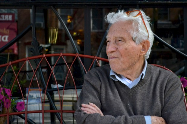 Vaccaro sitting in front of Long Island City's Manducatis Rustica. A collection of Vaccaro's work hangs in the restaurant, which he frequents up to five times a day. (Ariana Igneri/The Ink)
