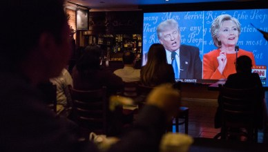 Attendees laugh, jeer, and eat as they watch the first 2016 Presidential Debate at Himalayan Yak in Jackson Heights, NY. (The Ink/Gabriela Bhaskar)