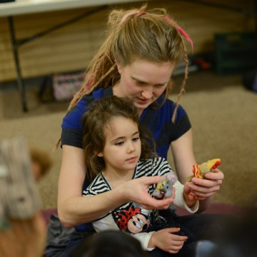 Heather Nickerson assists her niece, Journey Mitchell, during a singing exercise with puppets. The class Music-N-Motion is held at Jillian's Drawers on The Commons.