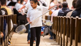 Hispanic Youth Group member Yelixa Hernandez helps collect donations during Mass at St. Willebrord Church in Green Bay, Wis., April 26. (CNS photo/Sam Lucero, The Compass)