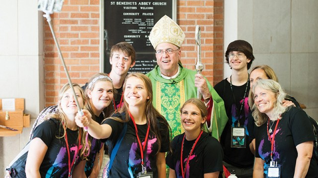 Some archdiocesan teens, part of the Northeast Kansas Rural Youth Council, pose with Archbishop Joseph F. Naumann for a picture with a selfie stick after the Life Teen Leadership Conference Mass at St. Benedict's Abbey in Atchison on June 25.  The teens are, from left, Marley Wareham, St. Dominic Parish, Holton; Sami Fischer, St. Stanislaus Parish, Rossville; Wade Minihan, St. Columbkille Parish, Blaine; Taylor Bittner, St. Stanislaus; Nikita Rogers, St. Francis Xavier Parish, Burlington; and Braden Myers, St. Francis Xavier. Also pictured are, second from right, Angie Bittner, archdiocesan rural youth ministry outreach coordinator, and Michelle Giesy, St. Patrick Parish, Osage City.  By Jessica Langdon