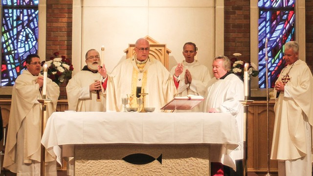Archbishop Joseph Naumann celebrates the 25th anniversary Mass of the Didde Catholic Campus Center in Emporia on Nov. 14. Pictured with the archbishop are, from left, Father Ray May; Father Curtis Carlson, OFM Cap.; Father Nick Blaha; Msgr. Gary Applegate; and Father Bill Porter.
