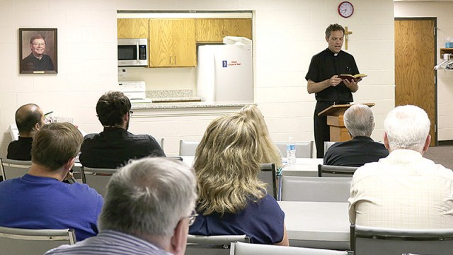 Father Greg Hammes, pastor of Most Pure Heart of Mary Parish in Topeka, reads the parable of the talents to open the parish's strategic planning meeting. The gathering helped the parish assess the best way in which to use its resources.