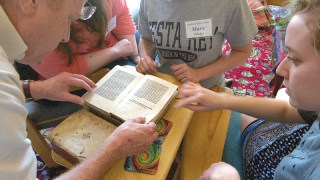 Chainy Folsom, left, Lindsey Weishar, right, and other students from the University of Missouri -Kansas City and the University of Missouri-Columbia, look at an antique book from the Mount St. Scholastica rare books collection. They also learned about bookbinding and script writing as part of their medieval studies coursework while staying with the Benedictine Sisters.
