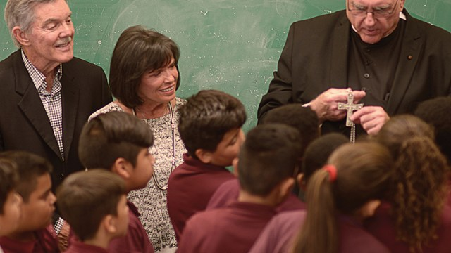 Tom and Sandy Long look on as Archbishop Joseph F. Naumann shows students at Christ the King School in Kansas City, Kansas, the pectoral cross he wears. The Longs are this year's Angels Among Us honorees for their contributions to Catholic education. LEAVEN PHOTO BY JILL RAGAR ESFELD