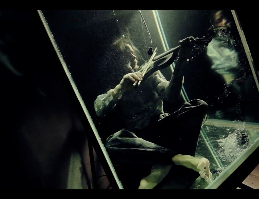 Between Music violinist playing underwater during AquaSonic