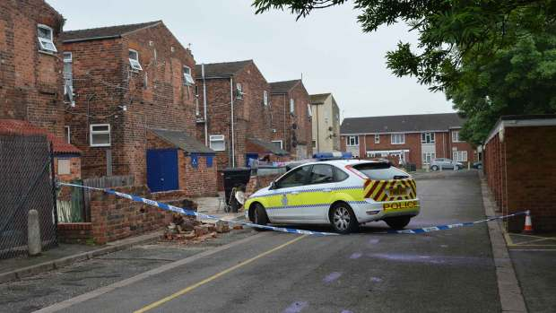Police officers carry out their enquiries at the back of Portland Street in Lincoln.