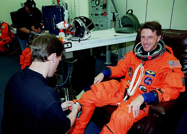In the suit-up room at Kennedy Space Center, Michael Foale smiles as a suit technician helps him don his launch and entry suit before liftoff on the STS-103 mission in December 1999. Photo: NASA
