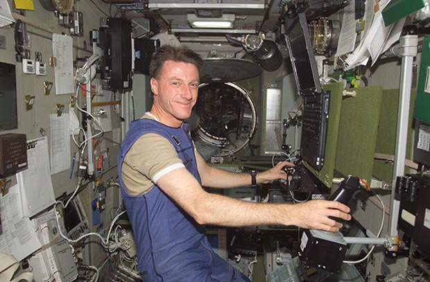 "Michael Foale, Expedition 8 mission commander and NASA ISS science officer, works with the Russian biomedical ""Pilot"" experiment (MBI-15) in the Zvezda Service Module on the International Space Station (ISS) in 2003. Photo: NASA"