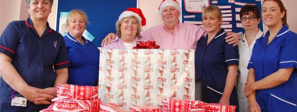 Lottery winners Jim and Maureen Emerton hand over their gifts to midwives and nurses from Nocton Ward(the neo-natal intensive care unit) at Lincoln County Hospital.
