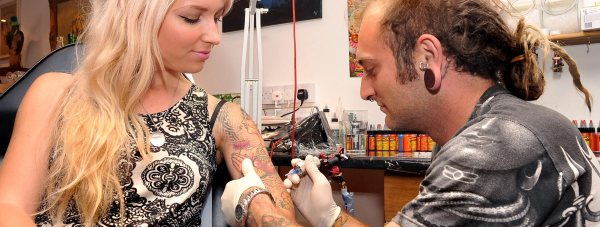 Alex Stark working a tattoo on his partner Katy-Jane Riches