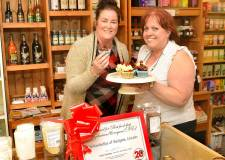 (L-R) Ashley Dalton of Adore in Gordon Road, couldn't resist a sweet treat when she popped across the road to congratulate Yellowbellys Linda Wardale on her success.