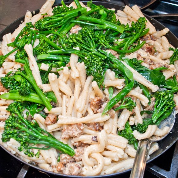Mixing in the pan Strozzapreti Pasta with Spicy Italian Sausage, Broccolini & Garlic Crema