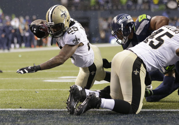 New Orleans Saints running back Khiry Robinson, left, runs for a 1-yard touchdown during the fourth quarter of an NFC divisional playoff NFL football game against the Seattle Seahawks in Seattle, Saturday, Jan. 11, 2014. (AP Photo/Elaine Thompson)