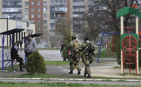 Armed pro-Russian activists walk through a children's playground near to the seized Ukrainian regional administration building in the eastern Ukrainian town of Slovyansk, Ukraine, Monday, April 14, 2014. Ukraine's acting president urged the United Nations on Monday to send peacekeeping troops to eastern Ukraine, where pro-Russian gunmen kept up their rampage of storming and occupying local government offices, police stations and a small airport. (AP Photo/Evgeniy Maloletka)