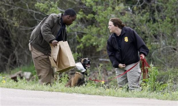 """Buddy,"" the scent dog for the Mississippi Fire Marshal's Office is offered a sniff of a particle of clothing belonging to a 9-year-old girl who authorities say is believed to have been swept away by flash flood waters along a Yazoo City, Miss., culvert, Monday, April 7, 2014. The dog was one of a number of participants in the search of the child who authorities say is believed to have been swept away by flash flood waters on Sunday. Yazoo County Director of Emergency Management Joey Ward said emergency crews, a dive team and volunteers searched rain-swollen drainage ditches until about midnight and resumed Monday. (AP Photo/Rogelio V. Solis)"