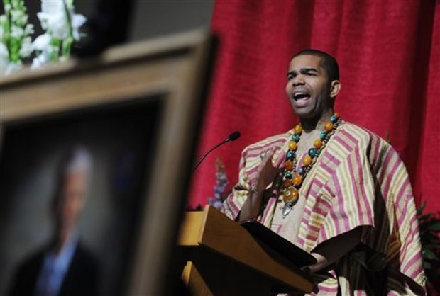 Chokwe Antar Lumumba, youngest son of late Jackson Mayor Chokwe Lumumba, stands near a portrait of his father while delivering a eulogy during the mayor's funeral service at the Jackson Convention Complex Saturday, March 8, 2014. (AP Photo/ The Clarion-Ledger, Joe Ellis)