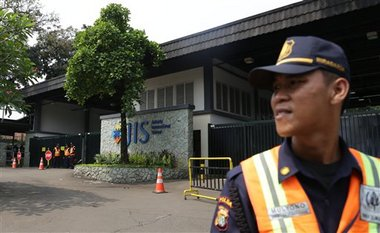 In this Thursday, May 8, 2014 photo, a security guard stands at the entrance of Jakarta International School (JIS) compound in Jakarta, Indonesia. U.S. citizen William Vahey taught here from 1992-2002. Vahey began his international teaching career with a series of stays around the Middle East and Europe, and by 1992, Vahey and his wife moved to Indonesia. He was one of the most beloved teachers in the world of international schools that serve the children of diplomats, well-off Americans and local elites. That was the public persona of William Vahey until a maid stole a memory drive from him in November. On it was evidence that Vahey molested scores of adolescent boys, possibly more. (AP Photo/Achmad Ibrahim)