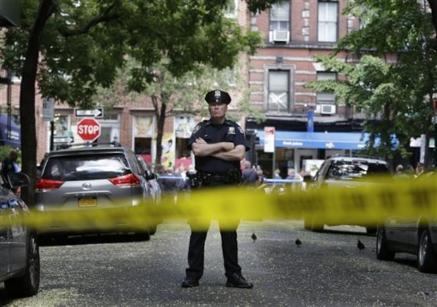 A police officer stands near a crime scene on Monday in New York. Authorities say a sex-assault suspect got in a shootout with law enforcement in New York City that wounded the suspect, two federal marshals and a police officer. (AP Photo/Seth Wenig)
