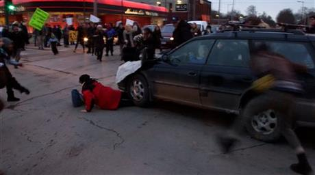 A car plows through a Ferguson rally after protesters blocked an intersection in South Minneapolis on Tuesday, Nov. 25, 2014. One woman was taken away by an ambulance. Two Minneapolis rallies to demonstrate against the grand jury's decision in Ferguson, Missouri, drew several hundred people carrying signs and chanting slogans in an effort to show solidarity with Michael Brown, the black teenager shot and killed by Ferguson police officer Darren Wilson in August.. (AP Photo/The Star Tribune, Mark Vancleave)