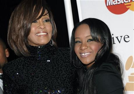 In this Feb. 12, 2011, file photo, singer Whitney Houston, left, and daughter Bobbi Kristina Brown arrive at an event in Beverly Hills, Calif. The daughter of late singer and entertainer Whitney Houston was found Saturday, Jan. 31, 2015, unresponsive in a bathtub by her husband and a friend and taken to an Atlanta-area hospital. The incident remains under investigation. (AP Photo/Dan Steinberg, File)