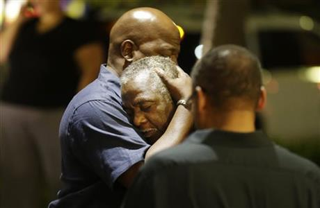 Worshippers embrace following a group prayer across the street from the scene of a shooting Wednesday, June 17, 2015, in Charleston, S.C. (AP Photo/David Goldman)