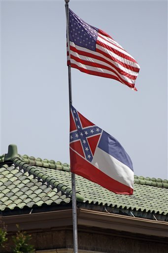 The state flag of Mississippi is unfurled underneath the American flag at the Secretary of State's Office building in downtown Jackson, Miss., Tuesday, June 23, 2015. Republican Lt. Gov. Tate Reeves said Tuesday, that Mississippi voters, not lawmakers, should decide whether to remove the Confederate battle emblem from the state flag. Reeves, who presides over the state Senate, spoke about the issue a day after Republican House Speaker Philip Gunn called the emblem offensive and said the state flag should change. (AP Photo/Rogelio V. Solis)
