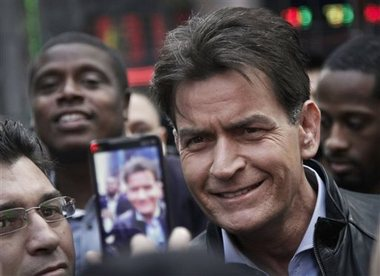 """In this Monday, Jan. 14, 2013, file photo, actor Charlie Sheen is mobbed for autographs and photos as he makes his way through Times Square in New York. In an interview Tuesday, Nov. 17, 2015, on NBC's """"Today,"""" Sheen said he tested positive for the virus that causes AIDS. Bebeto Matthews/AP File Photo"""