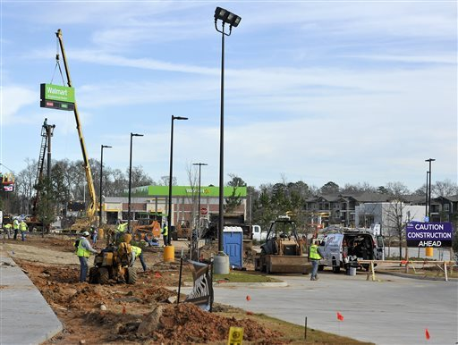 One crew finishes up landscaping as a second crew installs the primary sign on top of a pole, Friday, Jan. 15, 2016, at a new Wal-Mart Neighborhood Market location slated to open soon in Tyler, Texas. Even as the Bentonville, Ark., based company plans to open three stores in Tyler, the company announced Friday the planned closure of 269 stores, more than half of them in the U.S. and another big chunk in its challenging Brazilian market. (Andrew D. Brosig/Tyler Morning Telegraph)