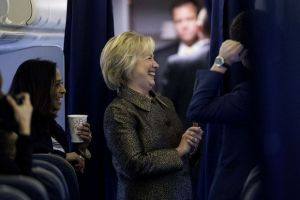 Democratic presidential candidate Hillary Clinton laughs aboard her campaign plane with Senior Policy Advisor Maya Harris, left, and other staff members in White Plains, N.Y., Sunday, Oct. 2, 2016. (AP Photo/Andrew Harnik)