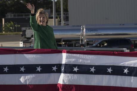 Democratic presidential candidate Hillary Clinton waves at reporters as she boards her campaign plane at an international airport, Sunday, Oct. 23, 2016, in Morrisville, N.C. (AP Photo/Mary Altaffer)