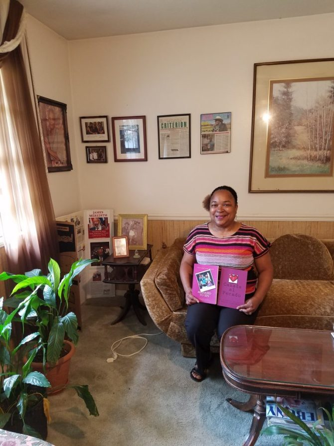 Meredith Coleman McGee, sits in the comfort of her home holding two copies of the book Married to Sin that she co-authored with Darlene D. Collier, sexual assault victim. The book has English and Spanish translations.  Photo By Janice K. Neal-Vincent