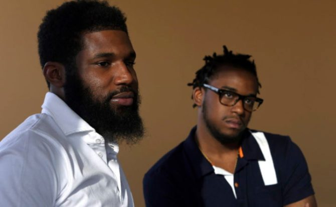 In this Wednesday, April 18, 2018 photo, Rashon Nelson, left, and Donte Robinson, right, listen to a reporter's question during an interview with The Associated Press in Philadelphia. (AP Photo/Jacqueline Larma)