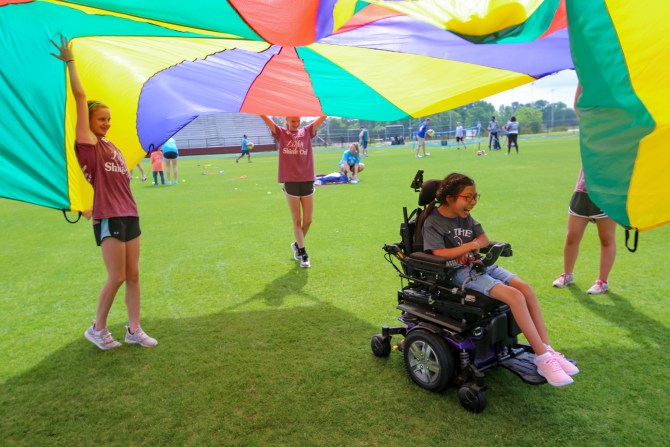 Raymond Elementary student Esther Williams enjoys playing under a parachute at special education field day at Hinds Community College on May 2. (April Garon/Hinds Community College)