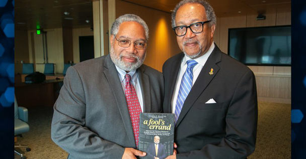 """Bunch (L) shares a copy of his book """"A Fool's Errand"""" with Benjamin Chavis Jr."""