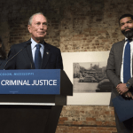 Democratic presidential candidate and former New York City Mayor Michael Bloomberg, center, speaks with members of the press following a roundtable on criminal justice reform led by Jackson, Mississippi Mayor Chokwe Antar Lumumba, far right, at the Smith Robertson Museum in downtown Jackson Tuesday, Dec. 3, 2019. Sarah Warnock/The Clarion-Ledger via AP