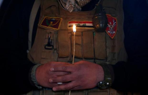 A security member holds a candle as he attends a mass on Christmas Eve at the Mar Shemoni church in the town of Bartella east of Mosul, December 24, 2016. REUTERS/Ammar Awad