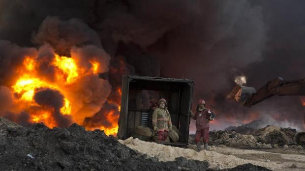 Firefighters work to quell an oil fire set by Islamic State militants in Qayara, south of Mosul, Iraq, on Monday, November 28, 2016. (AP Photo)