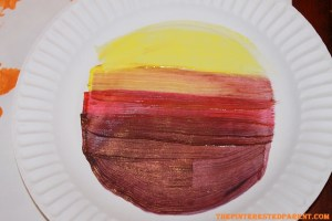 Paint another paper plate on the top side. Layer colors light to dark.