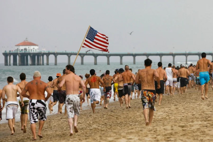 Participants run down the beach toward the Manhattan Beach pier during the first leg of the Iron Man competition on Saturday, July 4, 2009 in Hermosa Beach, Calif. Competitors haul themselves, flags, and beer into the air to celebrate Independence Day and show their patriotism as part of the Iron Man competition. In the Iron Man, a Hermosa Beach 4th of July tradition for 32 years, participants must run a mile, paddle board a mile, then chug a six-pack of beer, awards are given to those who do not puke Ð and those who puke the best. © 2009 Patrick T. Fallon