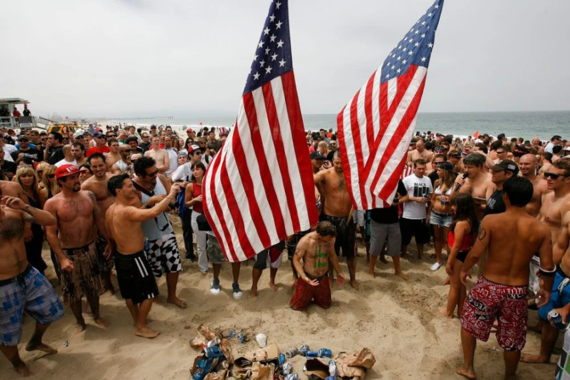 Participants in the Hermosa Beach Iron Man pour beer over each other as they hoist flags into the air at the end of the Iron Man competition on Saturday, July 4, 2009 in Hermosa Beach, Calif. Competitors haul themselves, flags, and beer into the air to celebrate Independence Day and show their patriotism as part of the Iron Man competition. In the Iron Man, a Hermosa Beach 4th of July tradition for 32 years, participants must run a mile, paddle board a mile, then chug a six-pack of beer, awards are given to those who do not puke Ð and those who puke the best. © 2009 Patrick T. Fallon