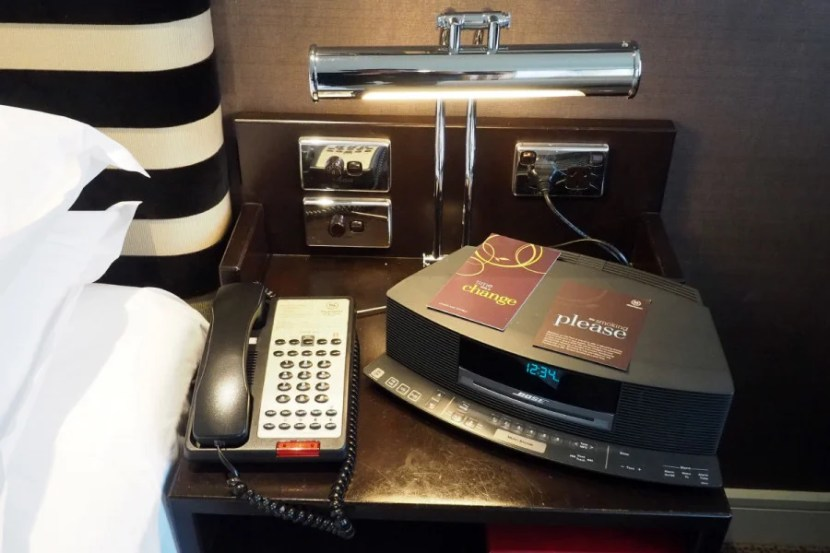 A Bose clock radio, phone, outlet and light controls were located next to the bed.